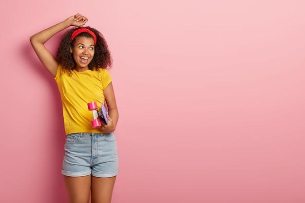 Hipster teenager-mädchen mit lockigem haar posiert im gelben t-shirt