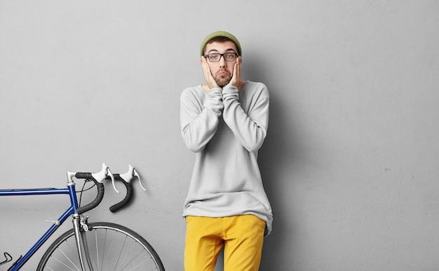 Hipster-typ mit überraschtem gesichtsausdruck, der modische kleidung trägt und in der nähe seines fahrrads steht