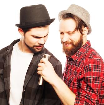 Hipster: zwei junge männer singen mit mikrofon. getrennt auf weiß.