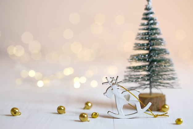 Hirschfigur, weihnachtsbaum und goldene kugeln auf dem tisch. weihnachtsdekorationen