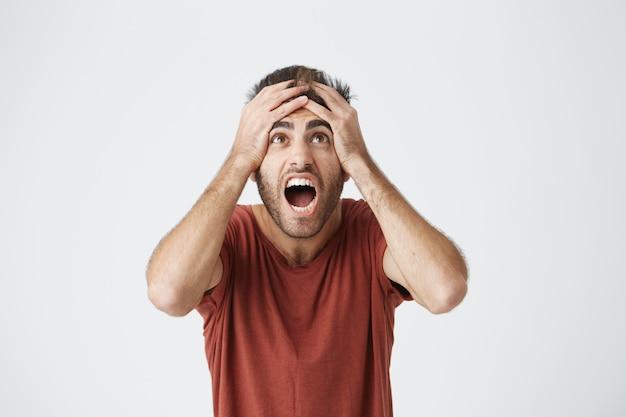 Hispanic bärtiger mann im roten hemd ausdrucksstark reagieren auf schlechte nachrichten von der arbeit, die über seinen chef sauer werden. unglücklicher kerl, der schreit, vom job gefeuert zu werden.