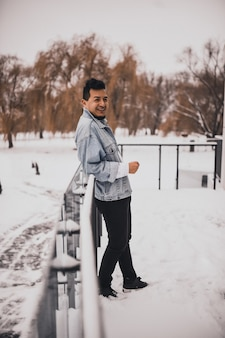 Hispanic brunette mann mit bart in jeansjacke im winter mitten im schnee