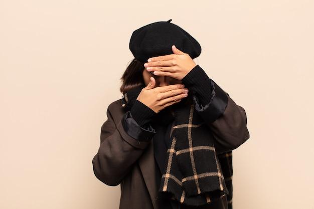 Hispanic frau bedeckt gesicht mit beiden händen, die nein zur kamera sagen! bilder ablehnen oder fotos verbieten