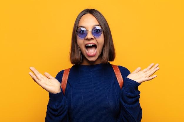Hispanic frau, die glücklich und aufgeregt aussieht, schockiert von einer unerwarteten überraschung mit beiden händen offen neben gesicht