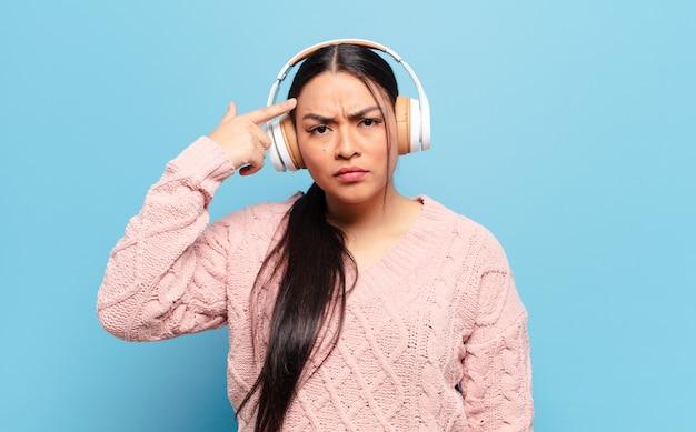 Hispanic frau, die sich verwirrt und verwirrt fühlt und zeigt, dass sie verrückt, verrückt oder verrückt sind