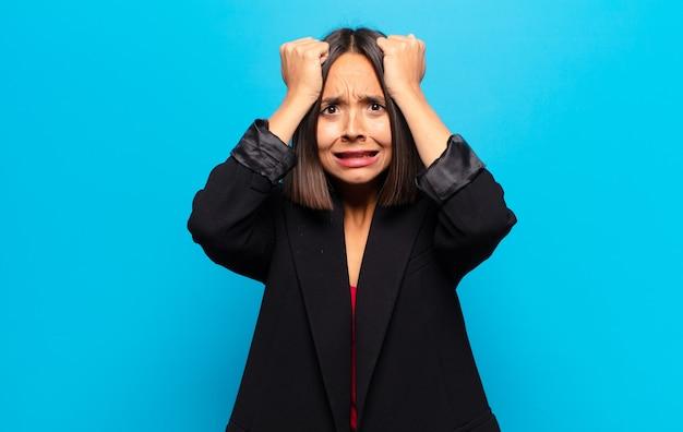 Hispanic frau fühlt sich gestresst und ängstlich, depressiv und frustriert mit kopfschmerzen und hebt beide hände an kopf