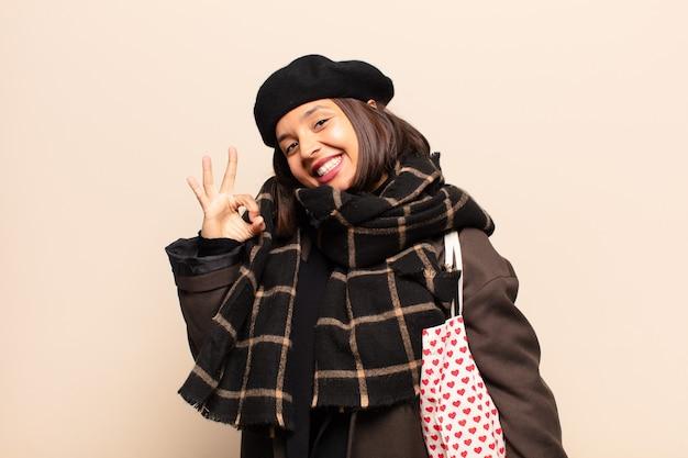 Hispanic frau fühlt sich glücklich, entspannt und zufrieden, zeigt zustimmung mit okay geste, lächelnd