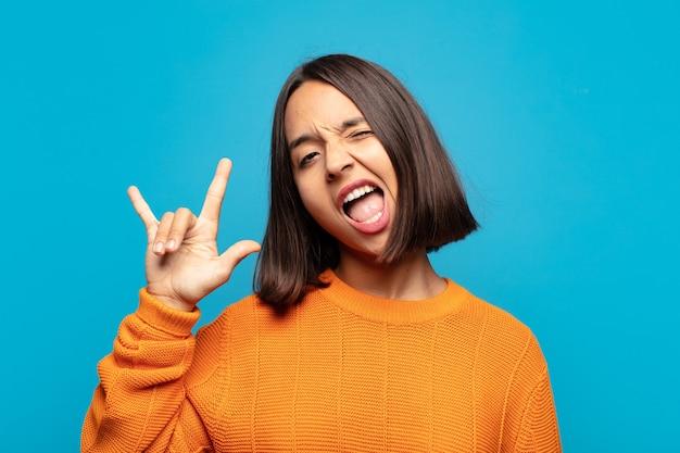 Hispanic frau fühlt sich glücklich, lustig, selbstbewusst, positiv und rebellisch, macht rock oder heavy metal zeichen mit der hand