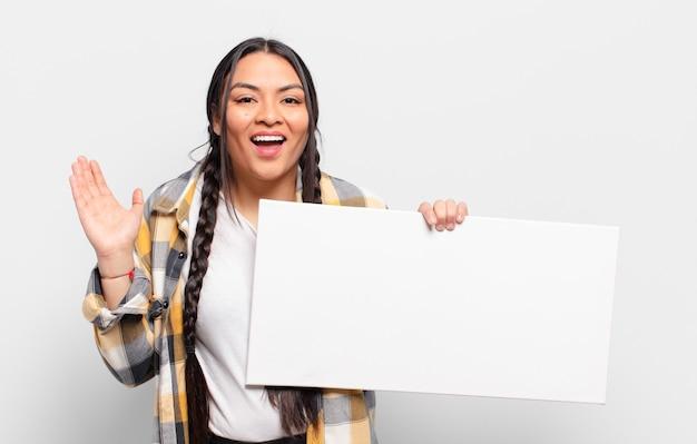 Hispanic frau fühlt sich glücklich, überrascht und fröhlich, lächelt mit positiver einstellung, realisiert eine lösung oder idee