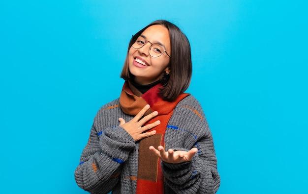 Hispanic frau fühlt sich glücklich und verliebt, lächelt mit einer hand neben dem herzen und der anderen nach vorne gestreckt