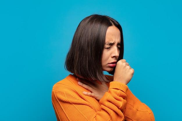 Hispanic frau fühlt sich krank mit halsschmerzen und grippesymptomen, husten mit bedecktem mund