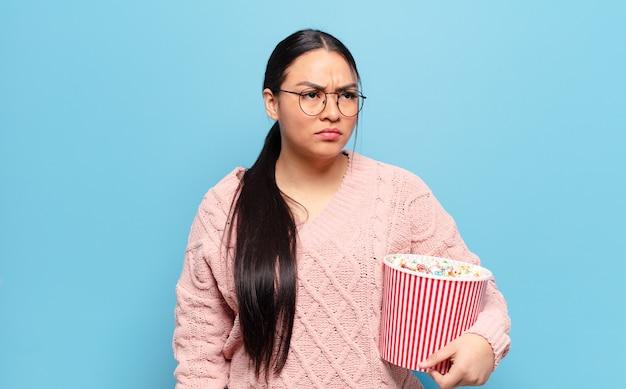 Hispanic frau fühlt sich traurig, verärgert oder wütend und schaut mit einer negativen einstellung zur seite, runzelt die stirn vor uneinigkeit