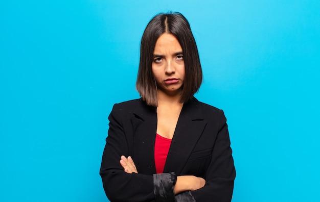 Hispanic frau fühlte sich unzufrieden und enttäuscht, sah ernst, genervt und wütend mit verschränkten armen