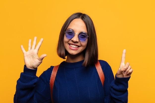 Hispanic frau lächelt und sieht freundlich aus, zeigt nummer sechs oder sechste mit der hand nach vorne, countdown
