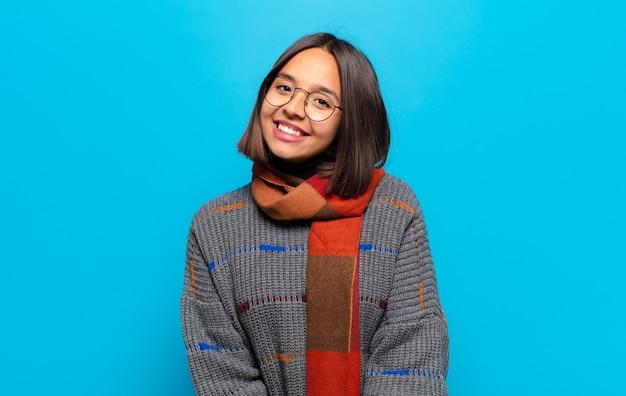Hispanic frau mit einem großen, freundlichen, sorglosen lächeln, positiv, entspannt und glücklich aussehend, chillend