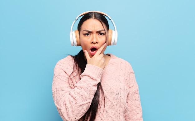 Hispanic frau mit mund und augen weit offen und hand am kinn, fühlt sich unangenehm geschockt, sagt was oder wow