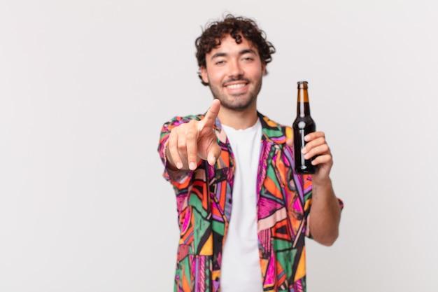 Hispanic mann mit bier zeigt auf die kamera mit einem zufriedenen, selbstbewussten, freundlichen lächeln, wählt sie