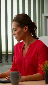 Hispanische dame, die früh morgens im modernen büro arbeitet. unternehmer, die bei der arbeit kommen, im professionellen arbeitsbereich, am arbeitsplatz in der persönlichen firma, die auf der computertastatur mit blick auf den desktop tippen