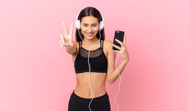 Hispanische fitnessfrau, die lächelt und glücklich aussieht, sieg oder frieden mit kopfhörern und einem telefon gestikuliert