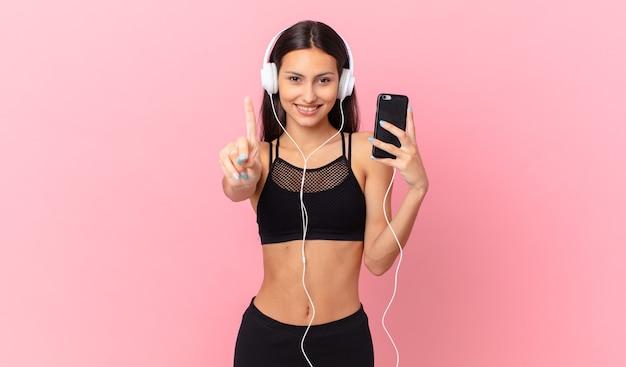 Hispanische fitnessfrau, die stolz und selbstbewusst lächelt und die nummer eins mit kopfhörern und einem telefon macht