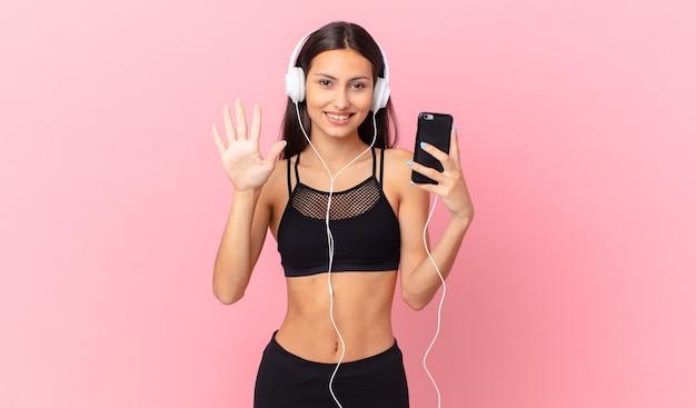 Hispanische fitnessfrau lächelt und sieht freundlich aus und zeigt nummer fünf mit kopfhörern und einem telefon