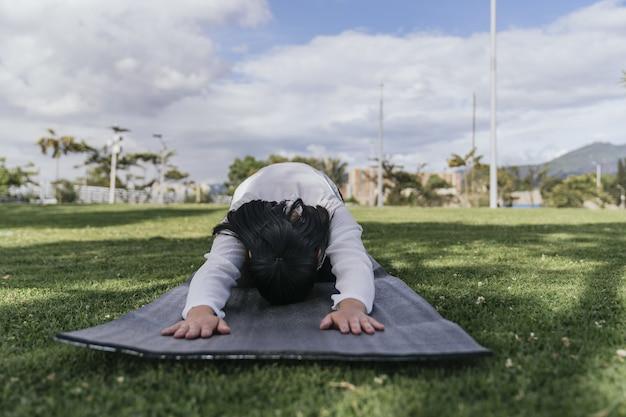 Hispanische frau beim yoga in einem park