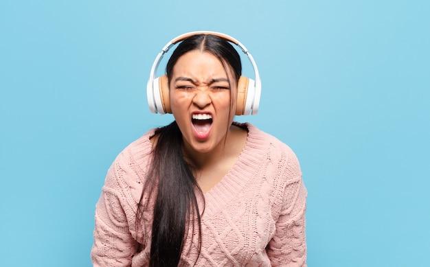 Hispanische frau, die aggressiv schreit, sehr wütend, frustriert, empört oder genervt aussieht und nein schreit