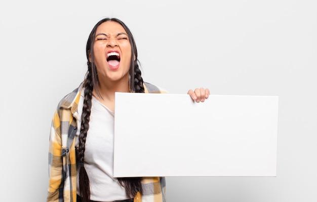 Hispanische frau, die aggressiv schreit und sehr wütend, frustriert, empört oder verärgert aussieht