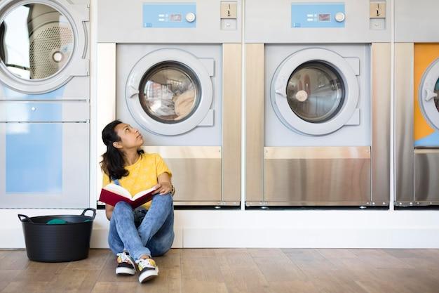 Hispanische frau, die auf dem boden sitzt und in der selbstbedienungswäscherei liest.