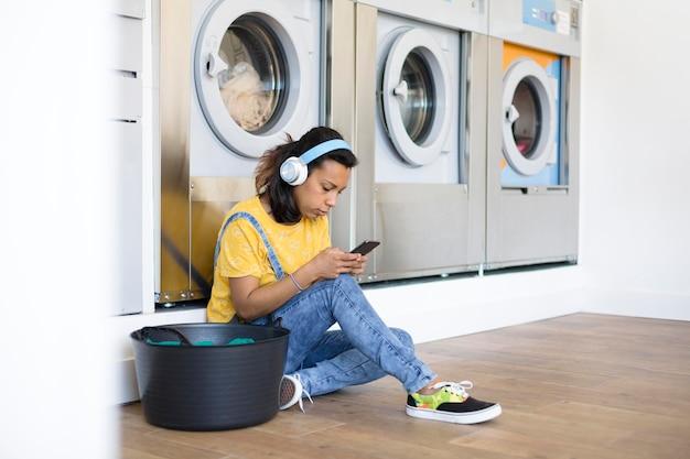 Hispanische frau, die auf dem boden sitzt und musik in der selbstbedienungswäscherei hört.