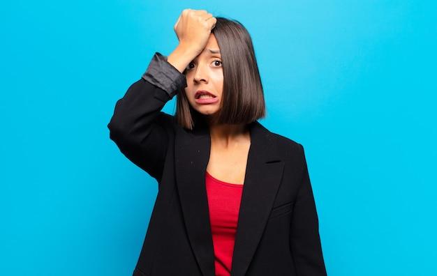 Hispanische frau, die die handfläche zur stirn hebt und denkt, oops, nachdem sie einen dummen fehler gemacht oder sich erinnert hat, fühlt sich dumm