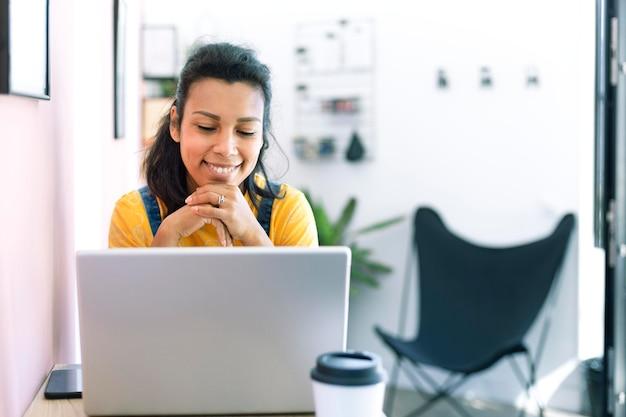 Hispanische frau, die einen laptop an ihrem arbeitsplatz benutzt.