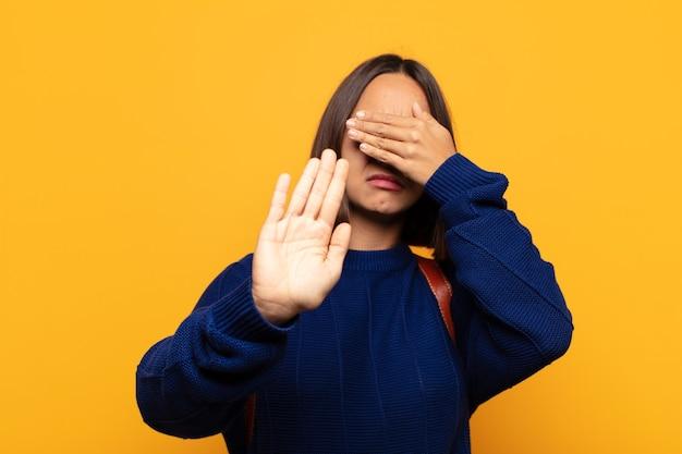 Hispanische frau, die gesicht mit hand bedeckt und andere hand nach vorne legt, um kamera zu stoppen, fotos oder bilder ablehnend