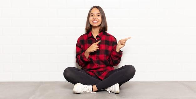 Hispanische frau, die glücklich lächelt und zur seite und nach oben zeigt, wobei beide hände objekt im kopienraum zeigen