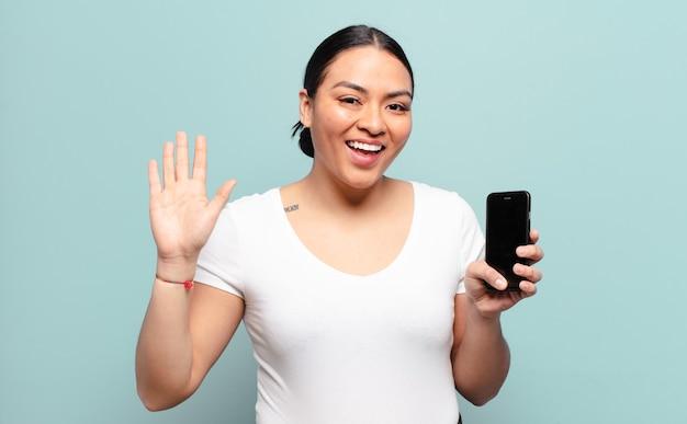 Hispanische frau, die glücklich und fröhlich lächelt, hand winkt, sie begrüßt und begrüßt oder sich verabschiedet