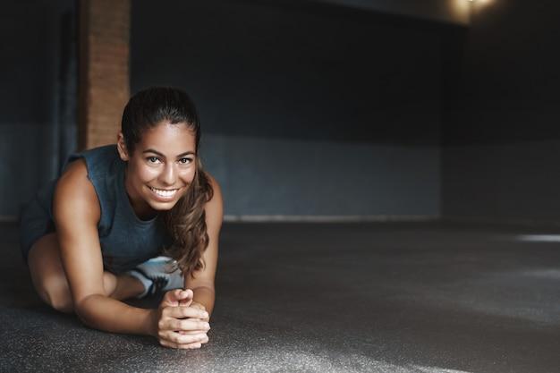 Hispanische frau, die körper auf dem boden fitnessstudio streckt