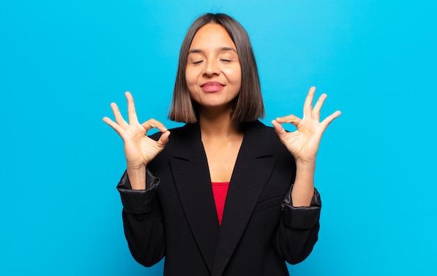 Hispanische frau, die konzentriert und meditierend aussieht, sich zufrieden und entspannt fühlt, denkt oder eine wahl trifft