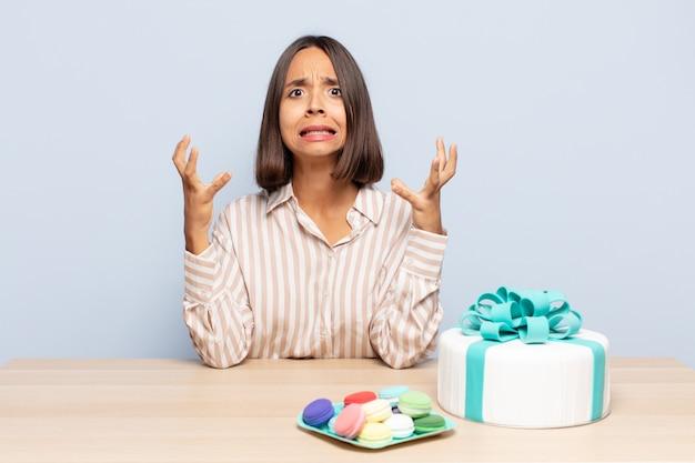 Hispanische frau, die mit den händen in der luft schreit, sich wütend, frustriert fühlt