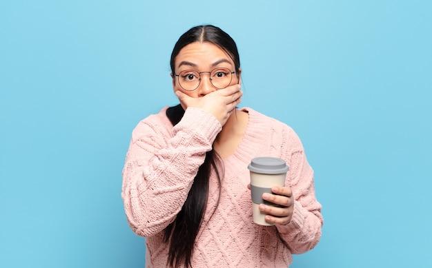 Hispanische frau, die mit einem schockierten, überraschten ausdruck den mund mit den händen bedeckt, ein geheimnis hält oder oops sagt
