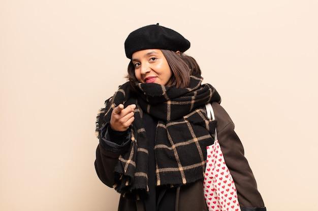 Hispanische frau, die mit einem zufriedenen, selbstbewussten, freundlichen lächeln auf die kamera zeigt und sie wählt