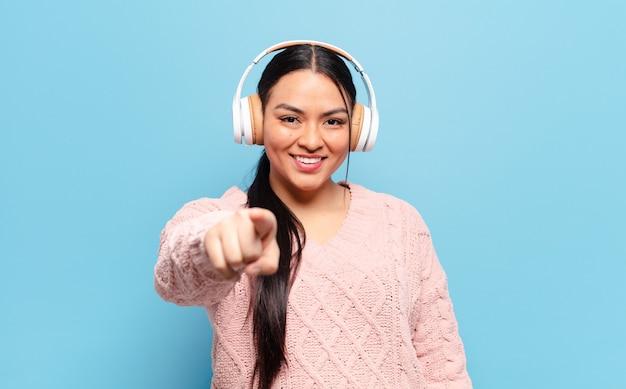 Hispanische frau, die mit einem zufriedenen, selbstbewussten, freundlichen lächeln auf kamera zeigt und sie wählt