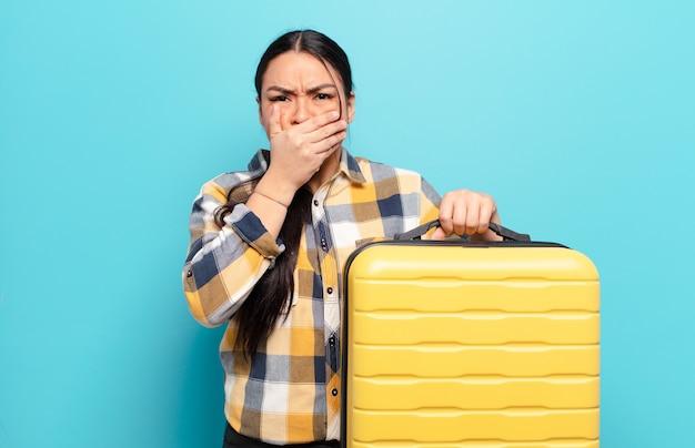 Hispanische frau, die mund mit händen mit einem schockierten, überraschten ausdruck bedeckt, ein geheimnis hält oder oops sagt