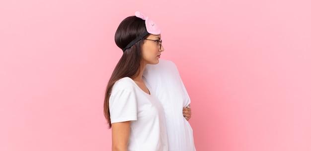 Hispanische frau, die pyjamas in der profilansicht trägt, denkt, sich vorstellt oder träumt und ein kissen hält