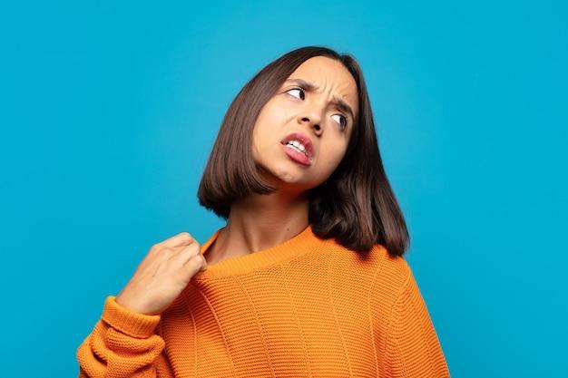 Hispanische frau, die sich gestresst, ängstlich, müde und frustriert fühlt und am hemdkragen zieht