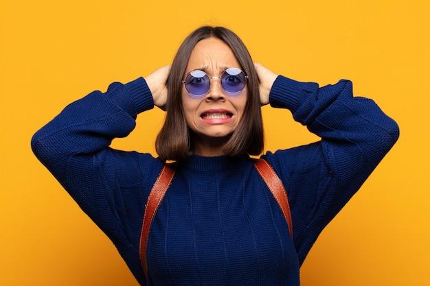 Hispanische frau, die sich gestresst, besorgt, ängstlich oder ängstlich fühlt, mit den händen auf dem kopf