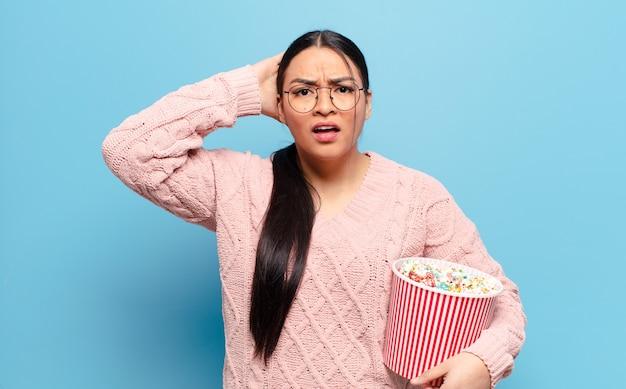 Hispanische frau, die sich gestresst, besorgt, ängstlich oder verängstigt fühlt, mit den händen auf dem kopf, die bei einem fehler in panik geraten
