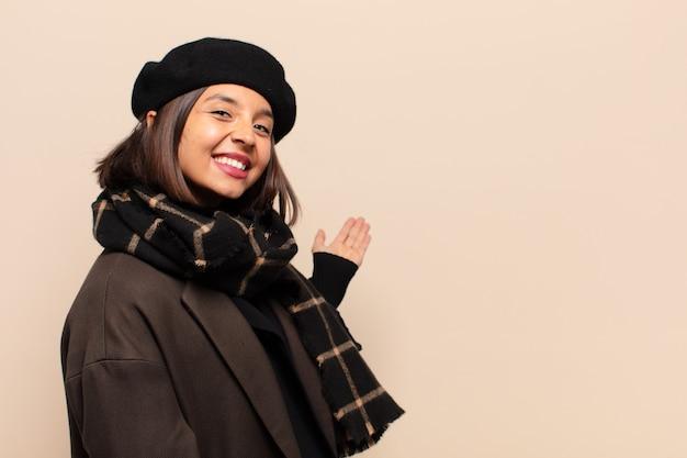 Hispanische frau, die sich glücklich und fröhlich fühlt, sie lächelt und begrüßt und sie mit einer freundlichen geste einlädt