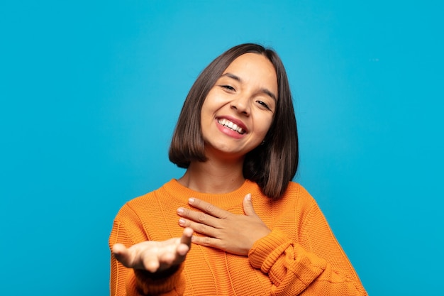 Hispanische frau, die sich glücklich und verliebt fühlt und mit einer hand neben dem herzen lächelt und die andere nach vorne ausgestreckt
