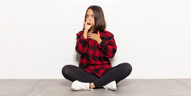 Hispanische frau, die sich mit halsschmerzen und grippesymptomen krank fühlt, husten mit bedecktem mund