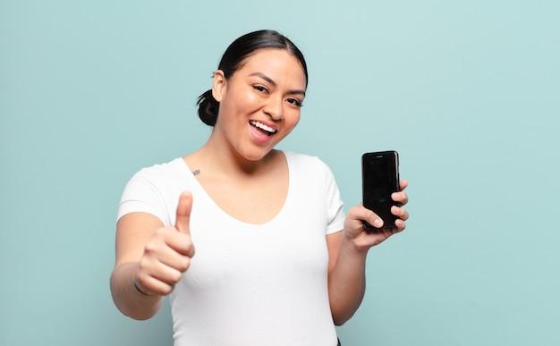 Hispanische frau, die stolz, sorglos, selbstbewusst und glücklich fühlt und positiv mit daumen hoch lächelt